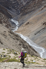 A woman is hiking toward a river, Spiti, India.