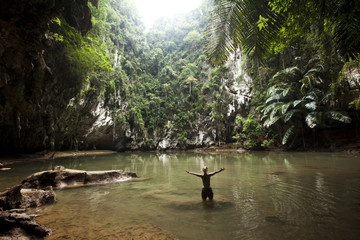 A beautiful young woman adventuring deep into a remote jungle pool relaxes in Thailand.
