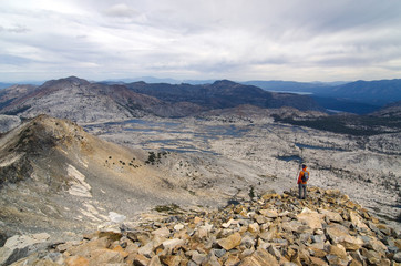 A male hiker looks over Lake Aloha, Desolation Wilderness and Lake Tahoe from the summit of Pyramid Peak, CA.