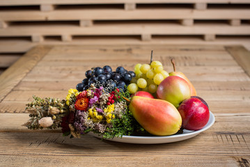 Fruit plate with wild flower decorations on the wood table. White and black grapes, apples, pears, plums on the platter