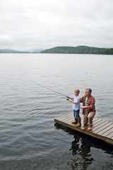 Senior man showing grandson how to fish off dock at Kezar Lake
