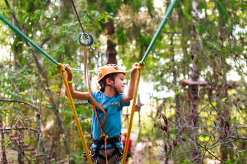 boy passes a rope obstacle course in the forest. cheerful child bravely overcomes extreme rope route outdoors. Ziplining