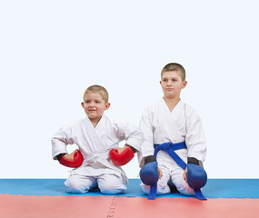 Two boys athletes in red and blue overlays sit on the mats
