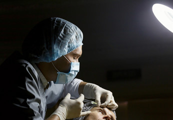 Doctor cosmetologist doing botox injection syringe. The doctor does an injection in the face of the cannula.
