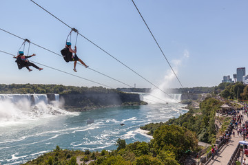 Wall Mural - Two Unrecognisable people taking zipline ride at Niagara Falls, Ontario, canada. New zipline in Niagara Parks opened in the summer of 2016