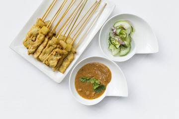 Grill pork satay with peanut sauce and cucumber salsa on white background