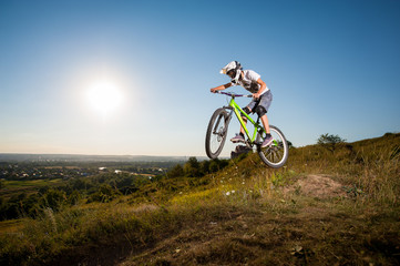 Man making extreme jump on a mountain bike on the hill against blue sky, sun and greenery into the distance. Cyclist is wearing white sportswear helmet and glasses.