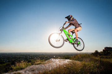 Bicyclist riding downhill and making extreme jump on a mountain bike into the distance from the slope in the mountains against blue sky with sun. Wide angle view