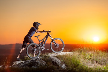 Male cyclist in helmets with mountain bike climbing up on the top of the hill against evening sky with bright sun at the sunset
