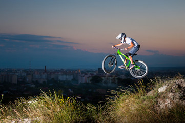 Rider in helmet and glasses flying on a mountain bike on the hill against evening sky and small town into the distance. Extreme downhill cycling.