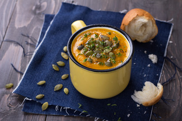 Pumpkin soup with pumpkin seeds and thyme in the cup on a wooden surface