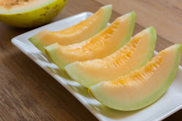 Slice of melon or cantaloupe on white plate on wood table background