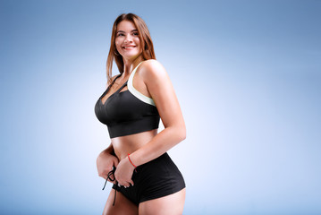 Plus size female model is posing in a fitness style in a studio