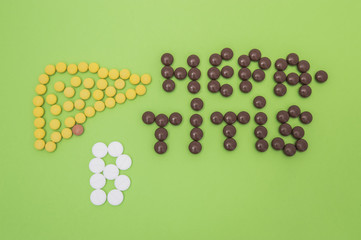 Figure or shape of human liver and the diagnosis of hepatitis B sign made of yellow, brown and white pills or tablets on a green paper background