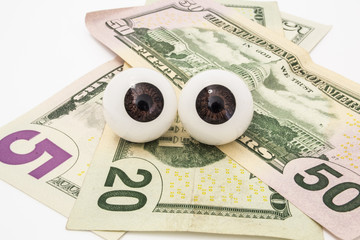 Pair of the eyes (eyeballs) lie on money (dollars) and look at object. Money is tracking you, watch out for your money close up front view. Illustration for use in business, finance, ophthalmology