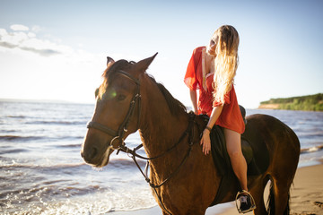Young beautiful blonde woman ride her horse near the river