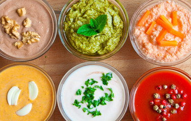 Various sauces in glass bowls on wooden table