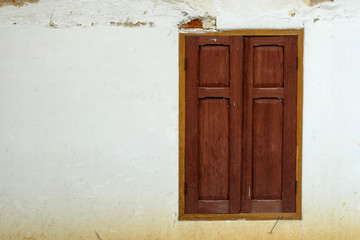 Wooden window on old white wall.