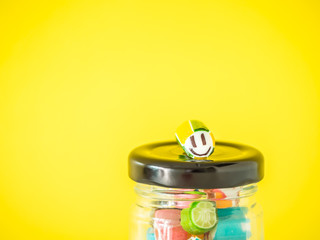 Closeup at smiley face candy cane put on the top of glass jar and yellow cement wall.