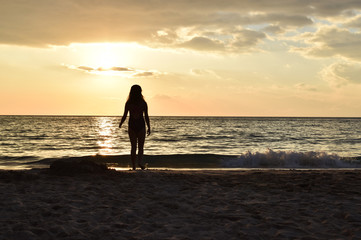 silhouette of a girl in the sunset light at the beach