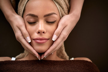 woman enjoying during facial massage in cosmetic salon