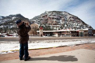 A little boy taking picture of a beautiful mountain covered with snow on Ouray,Colorado