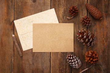pine cones and blank card on rustic wooden background