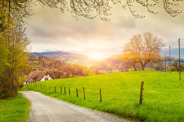 View of a spring day in the Switzerland, rural landscape at sunrise - Switzerland rural sunset landscape. Countryside farm, green field, sun light and cloud. Europe. Wall mural