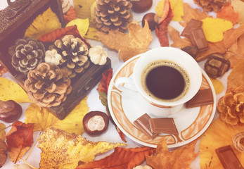 Cup of black coffee, chestnuts, pine cones and autumn leaves. Autumn background. Autumn scene. Coffee and autumn leaves. Fall background