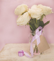 Roses on jar with pink breast cancer awareness ribbon and blank tag. Filtered image.,