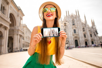 Young female tourist showing phone with photo standing in front of the famous Duomo cathedral in Milan