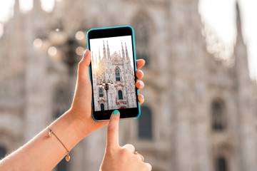 Female hands holding smart phone with photo of Duomo cathedral in the center of Milan city