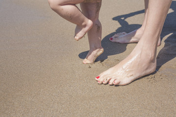 Mother and baby feet walking on sand beach