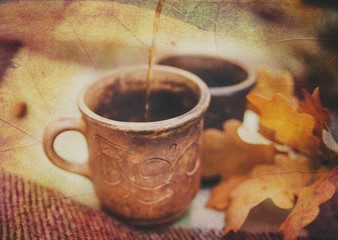Two Clay Rural Cups with Hot Beverage are on the Wool Plaid with Autumnal Leaves.Nature Background.Selective Focus.Toned