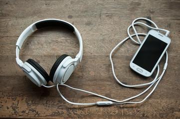 Casque audio blanc et smartphone sur table en vieux bois
