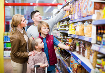 Family choosing cereal in supermarket.
