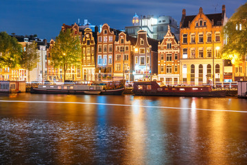 Canvas Prints Textures Amsterdam canal Amstel with typical dutch houses, houseboat and luminous track from the boat at night, Holland, Netherlands.
