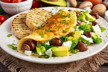 Mushroom, Feta Cheese egg Omelette witch Avocado, vegetables, lettuce, herbs and grilled bread.