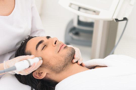 Guy having cavitation peeling at beauty salon