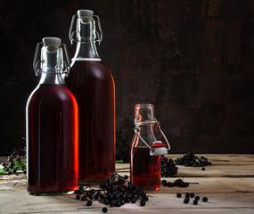 bottles with red juice of black elderberries (Sambucus nigra) on rustic wooden planks, dark background with copy space