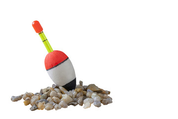 Fishing bobber on small stones with isolated background.