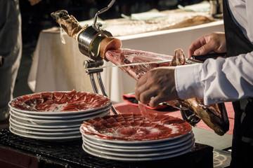 Cortador de jamón cortando un cinco jotas. degustación de jamón ibérico de bellota. Noches gastronómicas de verano.