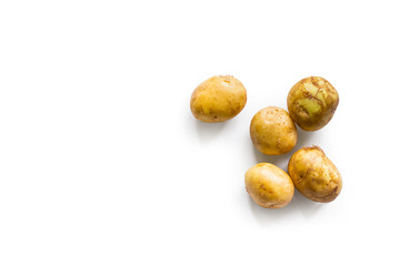 beautiful small rounded whole organic potatoes with the peel isolated on a white background seen from above