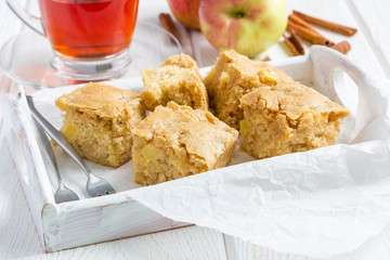 Homemade blondie brownies apple cake, square slices in wooden tray