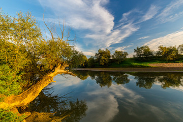 Mirror reflection of blue sky, clouds and sunset colors in wild river, in spring