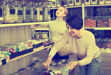 Women choosing dried herbs