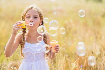 Cute child blowing soap bubbles in meadow