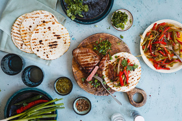 Mexican combo and flank steak, colorful pepper fajitas on flatbread over grey tabletop.