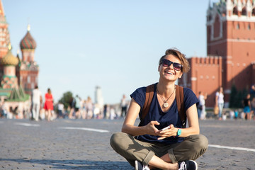 Young attractive woman traveler with backpack and mobile phone o