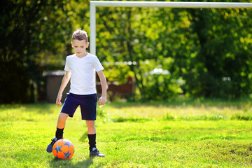 Little boy playing a soccer game on summer day